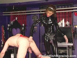 Mistress wearing black latex catsuit uses strapon on slave