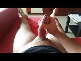 Moaning horny guy jerking off on the sofa