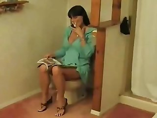 Cigarette smoking milf gets horny while sitting on the toilet