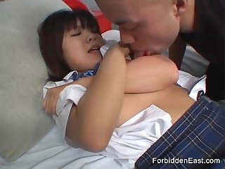 Cute young oriental in uniform gets her pert tits licked and sucked