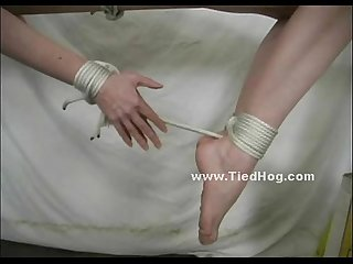 Redhead is tied up and has her thighs and the soles of her feet caned by a man
