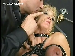 Blond slave with big tits gets her tits tied together with rope in a dungeon by german master