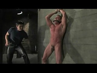Athletic strong guy tied on wall bdsm